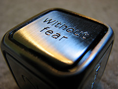 """A metal die with the words: \""""Without fear\"""" on the top face."""