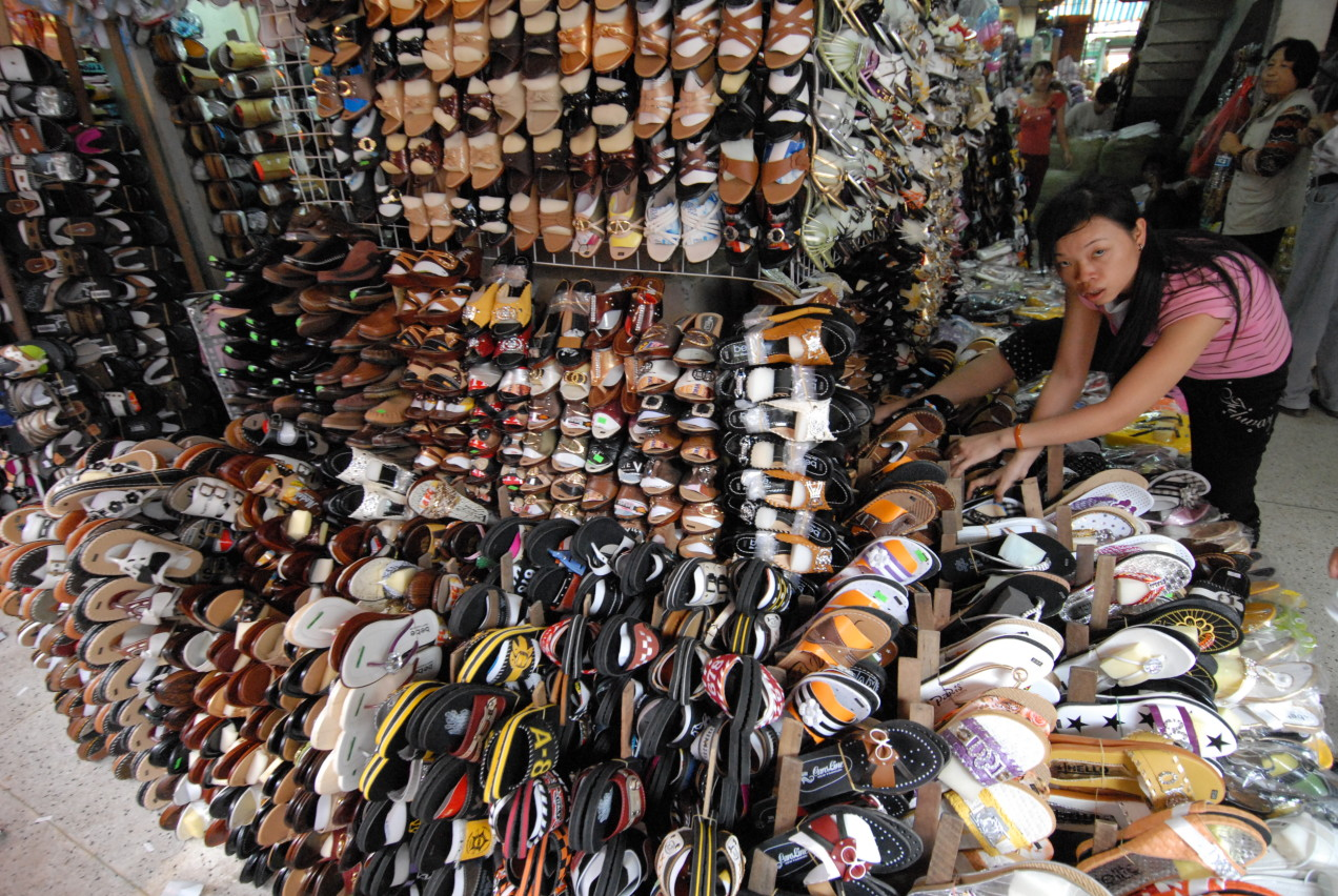 Woman manuevering though a huge tower of shoes